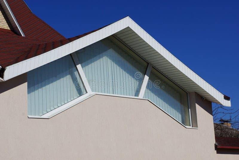 Grande fenêtre sur le mur en béton gris du grenier sous le toit de tuile rouge contre le ciel bleu image libre de droits