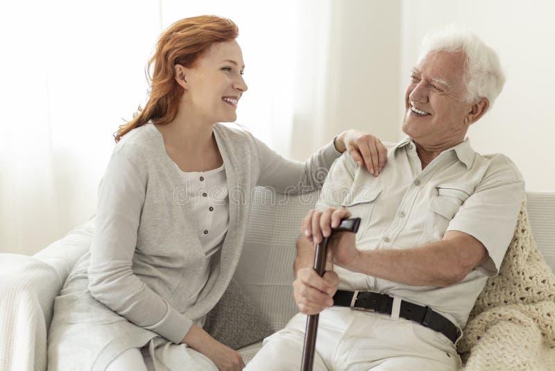 Grande-filha que ri com seu avô ao sentar-se em um sofá imagem de stock royalty free