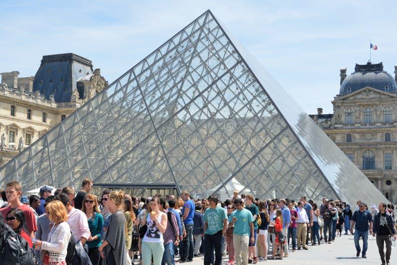Grande folla che fa la coda il museo esterno del Louvre fotografie stock
