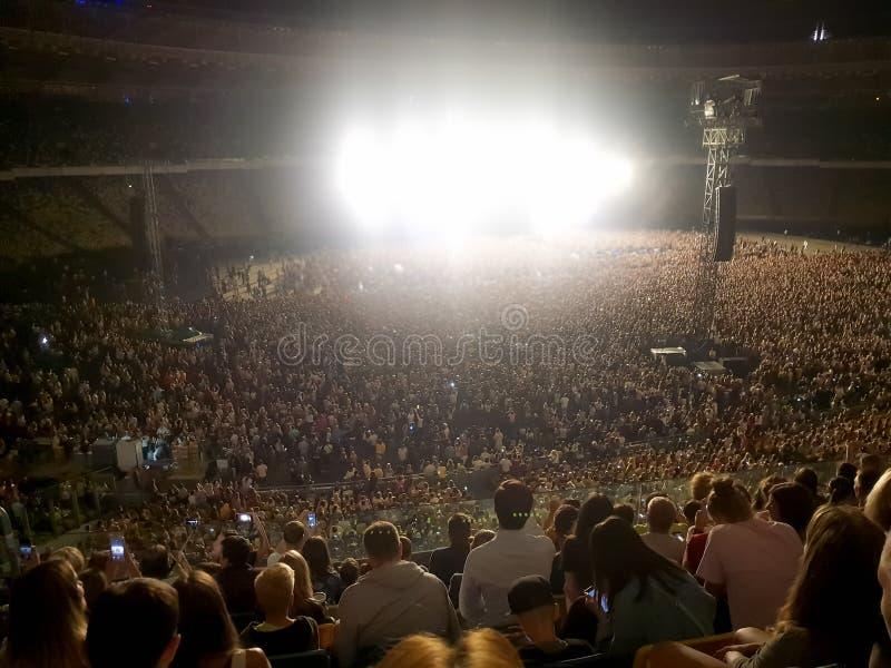 Grande folla dei fan che si siede sulle tribune dello stadio e che ascolta il concerto di musica rock alla notte Luce intensa e l immagini stock