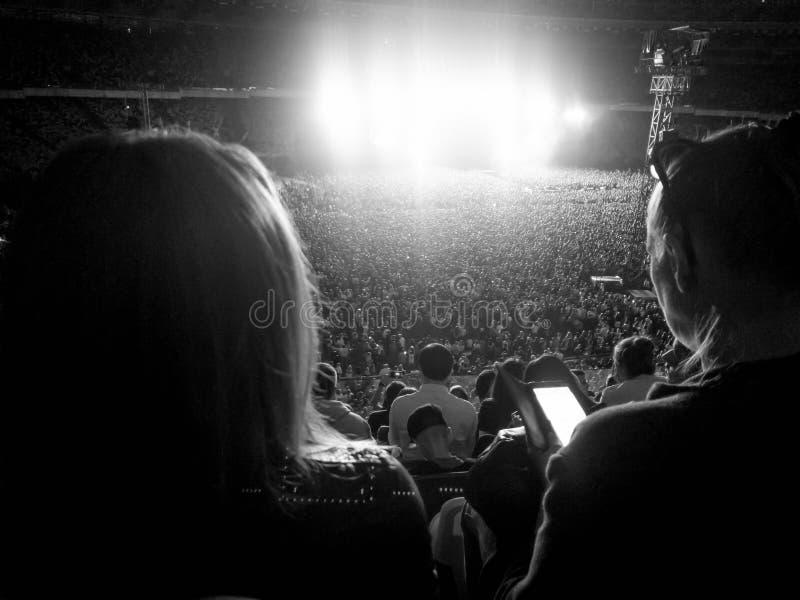 Grande folla dei fan che si siede sulle tribune dello stadio e che ascolta il concerto di musica rock alla notte Luce intensa e l fotografia stock libera da diritti