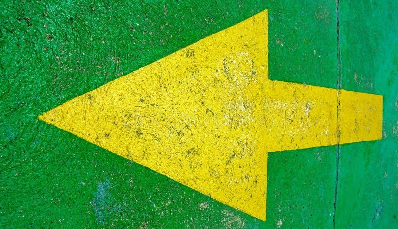 Grande freccia gialla che indica a sinistra con il fondo verde immagine stock
