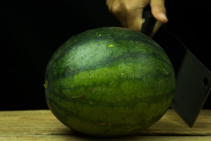 Grande goccia dell'anguria su legno, su un fondo nero fotografia stock libera da diritti