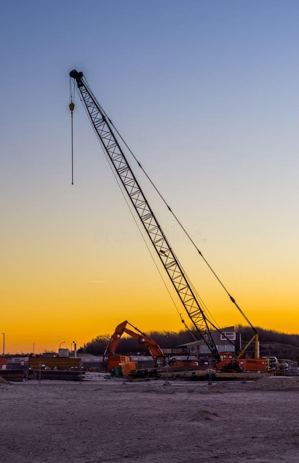 Grande gru di costruzione con gli escavatori alla spiaggia durante il tramonto, cantiere alla spiaggia immagine stock libera da diritti
