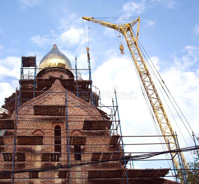 Grande gru a torre gialla sulle costruzioni russe della chiesa fotografie stock