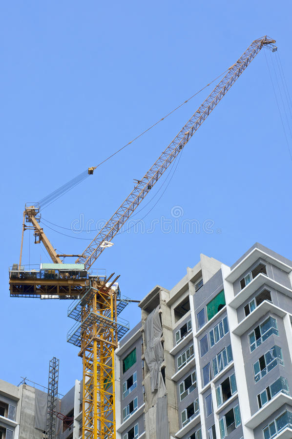 Grande grue et gratte-ciel inachevé avec le ciel bleu image libre de droits
