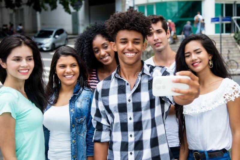 Grande grupo de adultos novos internacionais que tomam o selfie com pho imagens de stock royalty free