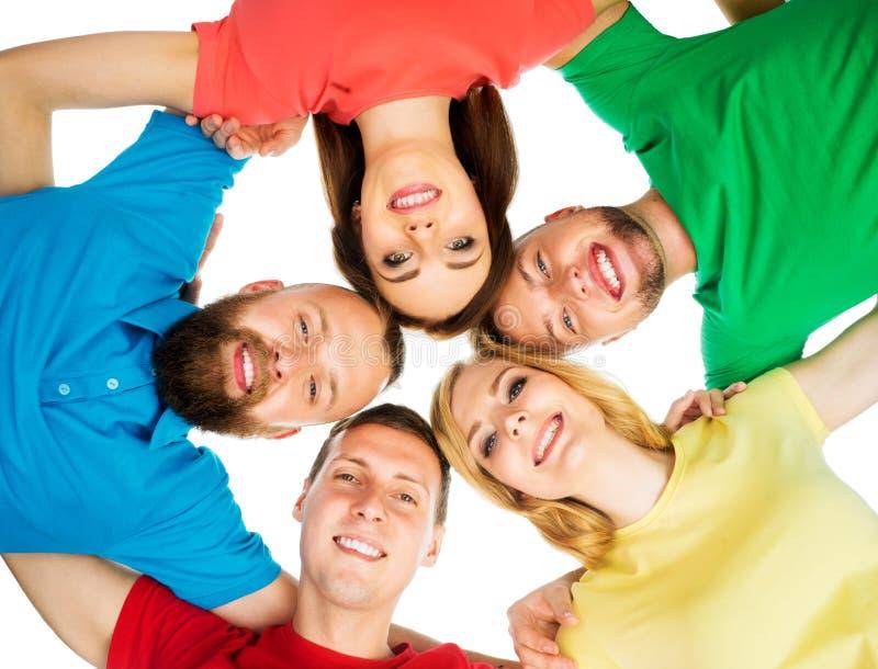Grande grupo de amigos de sorriso que ficam junto e que olham a câmera isolada no fundo branco imagem de stock royalty free