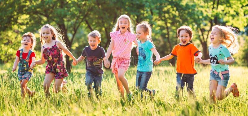 Grande grupo de crianças, de meninos dos amigos e de meninas correndo no parque no dia de verão ensolarado na roupa ocasional imagem de stock royalty free