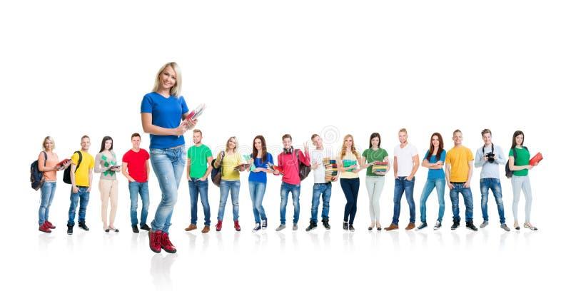 Grande grupo de estudantes adolescentes no branco imagem de stock