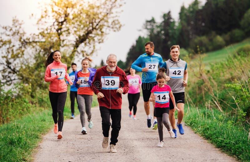 Grande grupo de multi povos da geração que correm uma competição da raça na natureza foto de stock royalty free