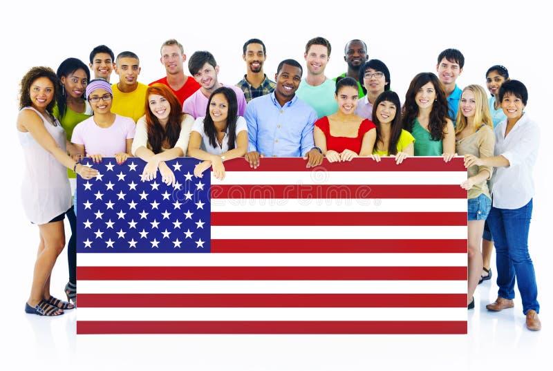 Grande grupo de pessoas que guarda a placa da bandeira americana foto de stock