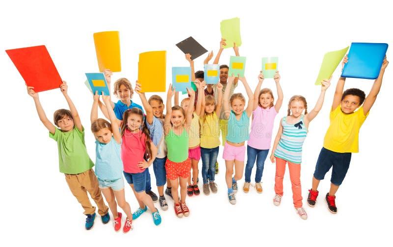 Grande grupo diverso de crianças que levantam acima dos livros de texto fotos de stock