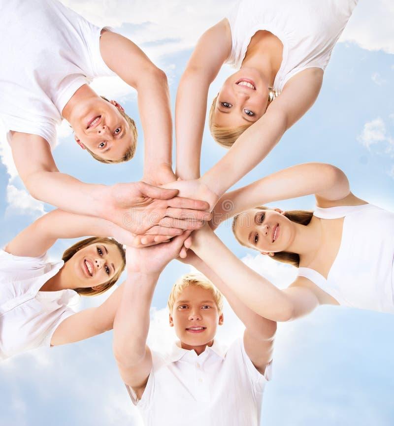 Grande gruppo di amici adolescenti sorridenti che esaminano macchina fotografica immagine stock libera da diritti