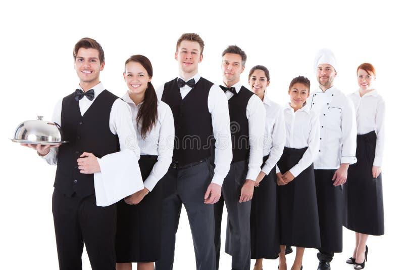 Grande gruppo di camerieri e di cameriere di bar che stanno nella fila immagini stock libere da diritti