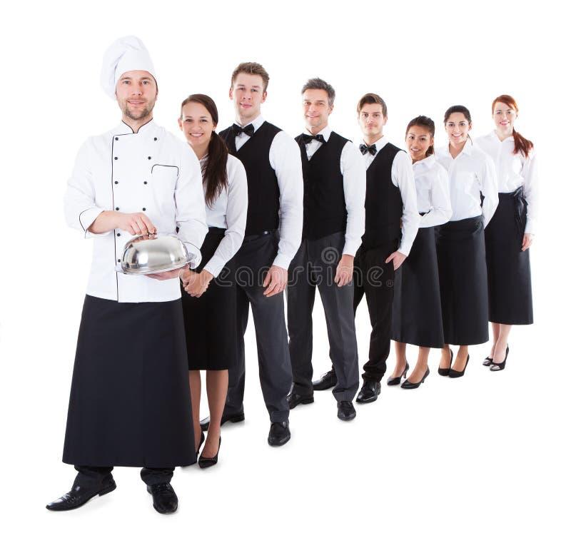Grande gruppo di camerieri e di cameriere di bar che stanno nella fila fotografia stock libera da diritti
