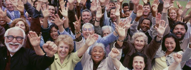 Grande gruppo di gente multi-etnica che incoraggia con le armi alzate immagine stock