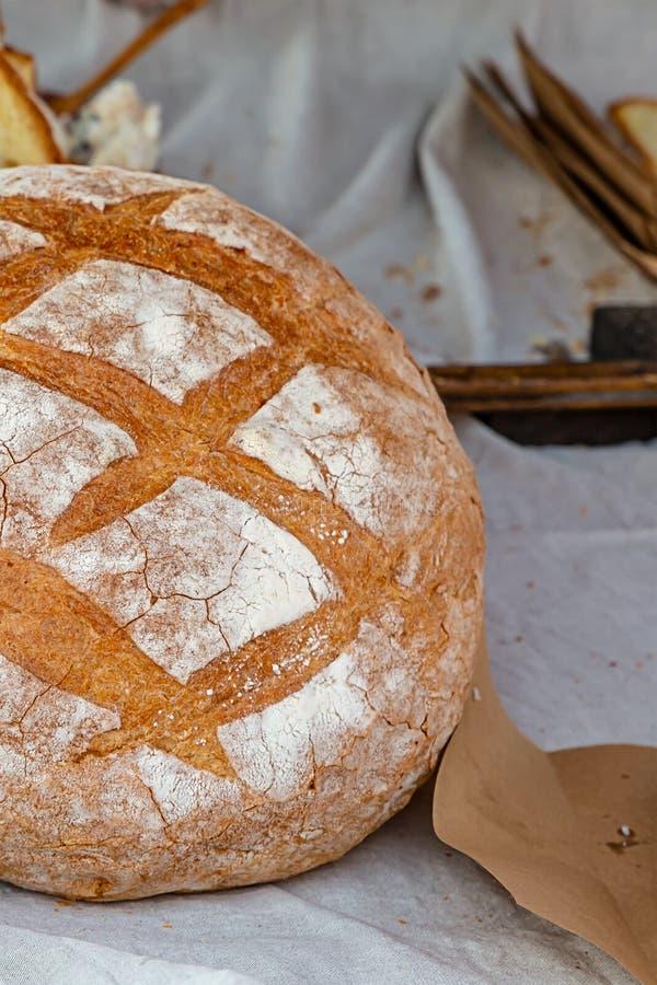 Grande ha cotto il rotolo rustico con la crosta marrone spruzzata con il pane tostato delizioso del panino della base della farin fotografia stock libera da diritti