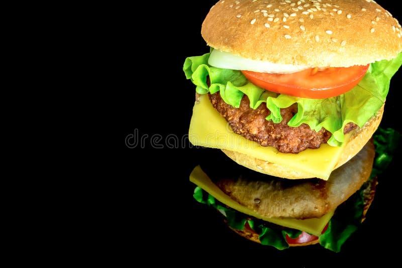 Grande hamburger con gli ortaggi freschi con la riflessione isolati su fondo nero Foto luminosa immagini stock