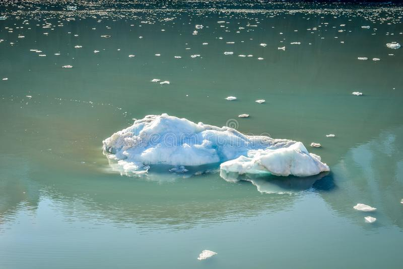 Grande iceberg e muitas partes minúsculas que flutuam e que derretem afastado fotografia de stock