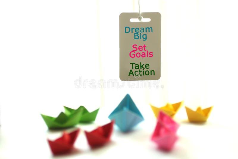 Grande ideal, ajustou objetivos, toma a a??o Um memorando criativo e uns barcos de papel imagens de stock royalty free