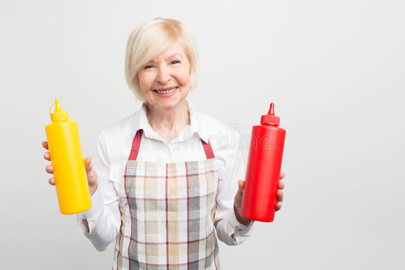 Grande imagem da mulher adulta que guarda duas garrafas dos sauses em suas mãos Quer cozinhar algum alimento saboroso para ela am fotografia de stock royalty free