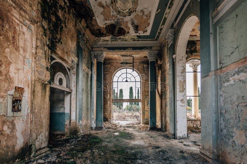 Grande interior arruinado do salão coberto de vegetação por plantas e por musgo imagem de stock