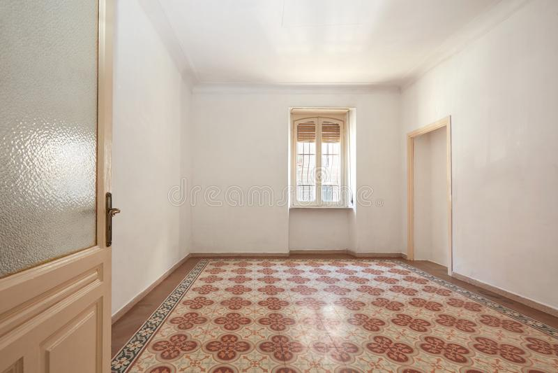 Grande interno vuoto della stanza con il vecchio pavimento piastrellato geometrico fotografia stock