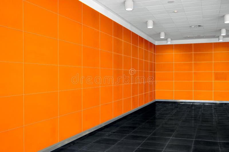 Grande interno vuoto della stanza con la parete arancio luminosa, soffitto a del whire immagine stock