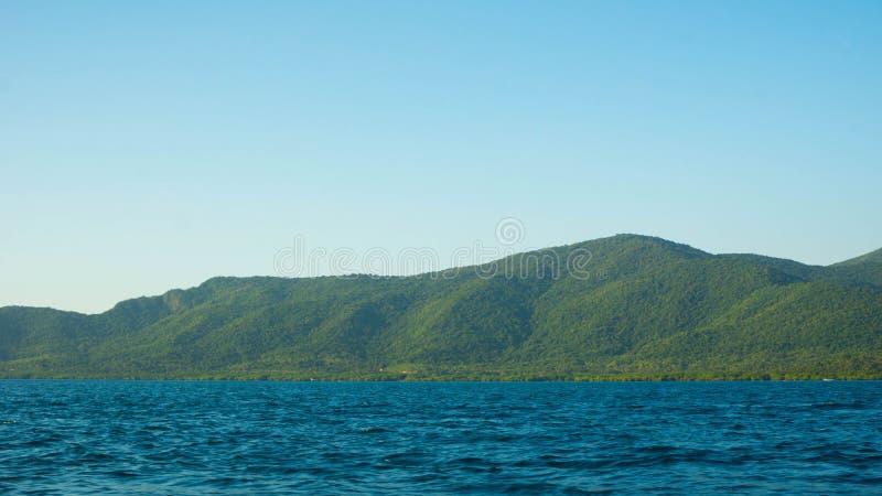 Grande isola con il mare scuro blu profondo e chiaro cielo in paese tropicale immagini stock