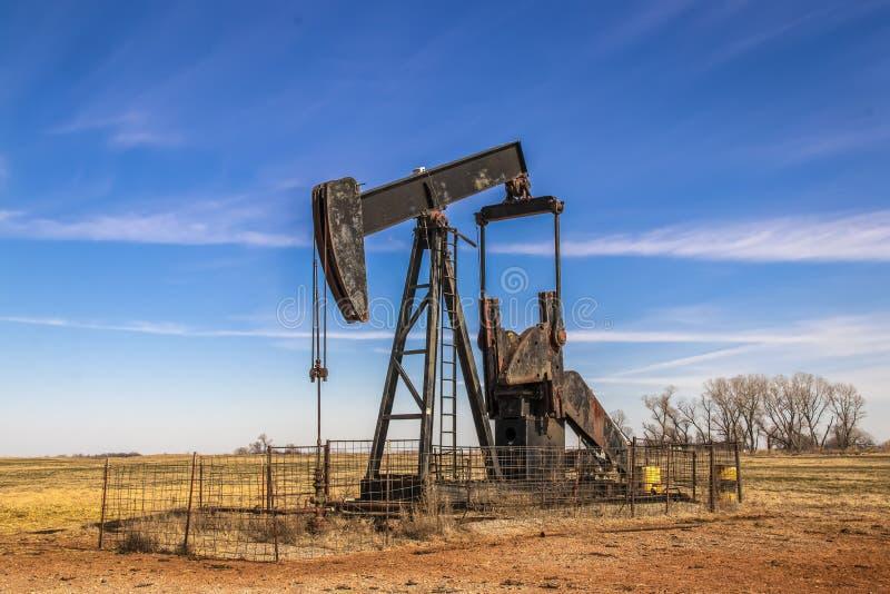 Grande jaque oxidado velho da bomba de poço de petróleo cercado pela cerca do painel do gado para fora no campo com o céu muito a imagens de stock royalty free