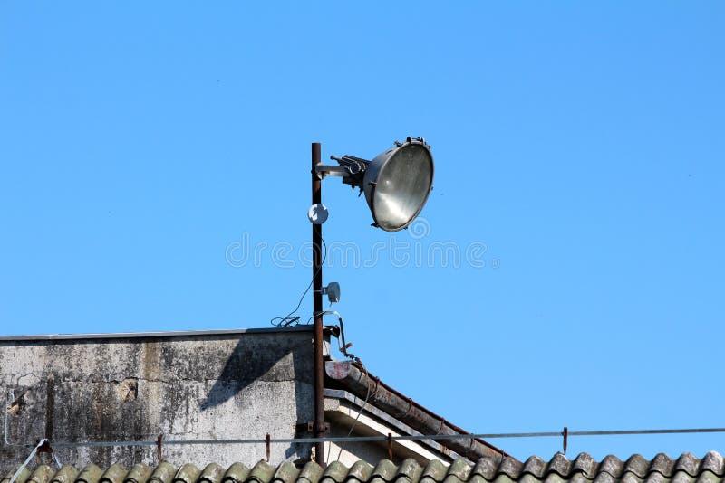 Grande lampada industriale di stile montata sul palo arrugginito del metallo alla cima di costruzione nel complesso industriale a fotografia stock libera da diritti