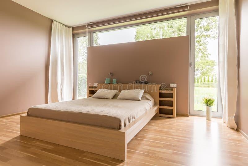 Grande letto con il piumino beige immagini stock libere da diritti