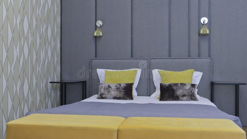Grande letto in una camera da letto di lusso moderna dell'appartamento, nel grey fotografie stock libere da diritti