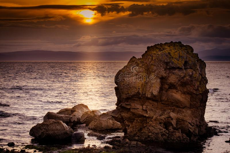 Grande linea costiera rocciosa a Dunoon sulla notte di fine dell'estate immagine stock libera da diritti