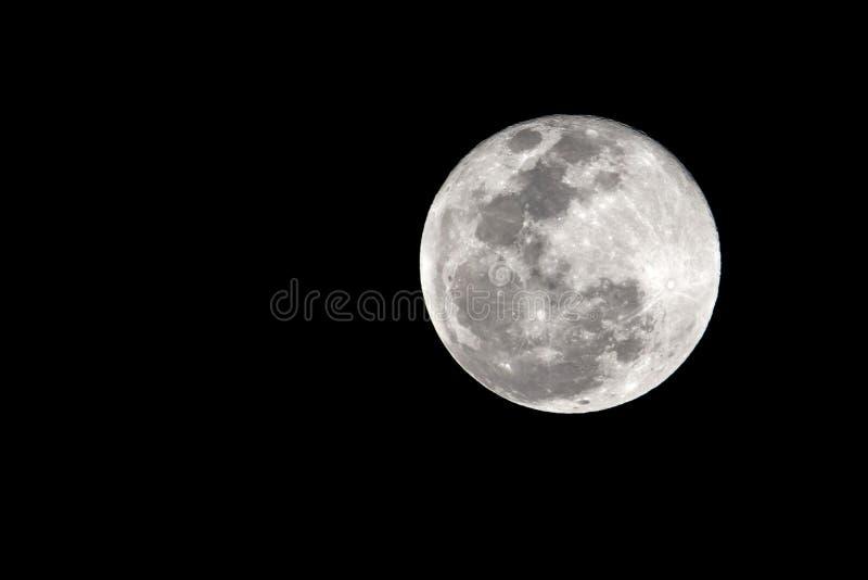 Grande luna nella sua fase completa con i crateri dettagliati visibili sui suoi bordi, tutti in un fondo nero, preso con grande t immagini stock
