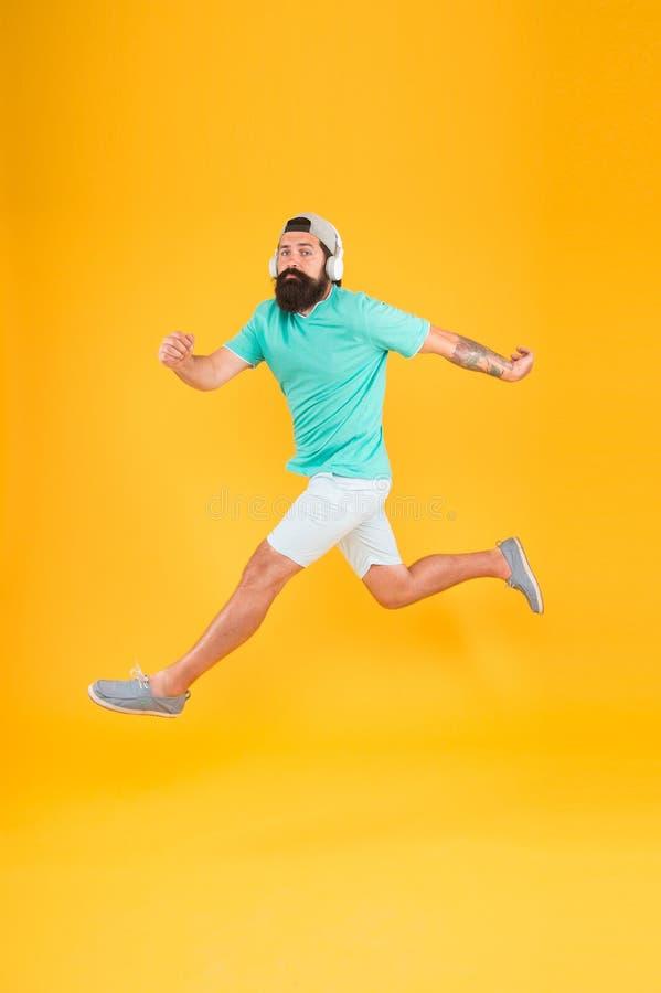 Grande música para dançar Homem do dançarino que move-se para a música no fundo amarelo O homem farpado aprecia a dança do salto  fotos de stock royalty free