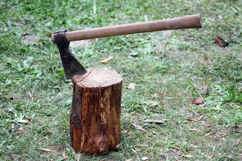 Grande machado com a lâmina do aço sobre o log de madeira imagem de stock royalty free