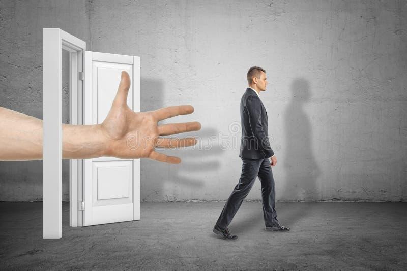 Grande main ouverte masculine accédant par la porte blanche au jeune homme d'affaires qui marche loin sur le fond gris de mur photographie stock libre de droits