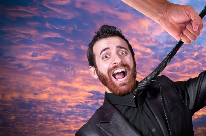 Grande main saisissant la cravate du jeune homme d'affaires images libres de droits
