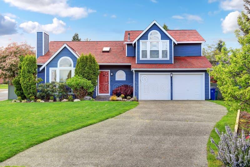 Grande maison bleue avec l'équilibre blanc et une pelouse gentille images libres de droits