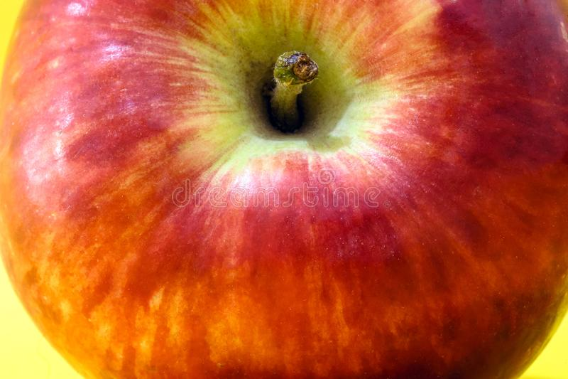 Grande mela rossa con fondo giallo fotografia stock