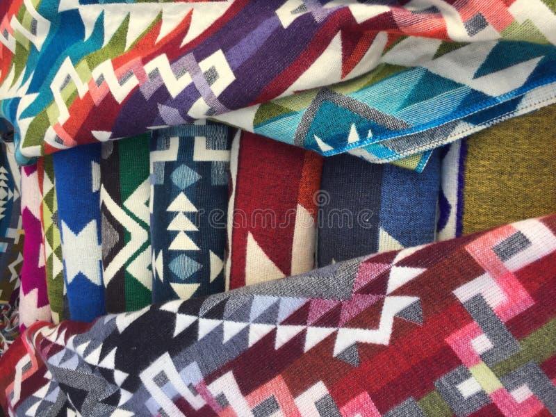 Grande mucchio dei tessuti andini variopinti tipici trovati al mercato famoso di Otavalo nell'Ecuador immagine stock