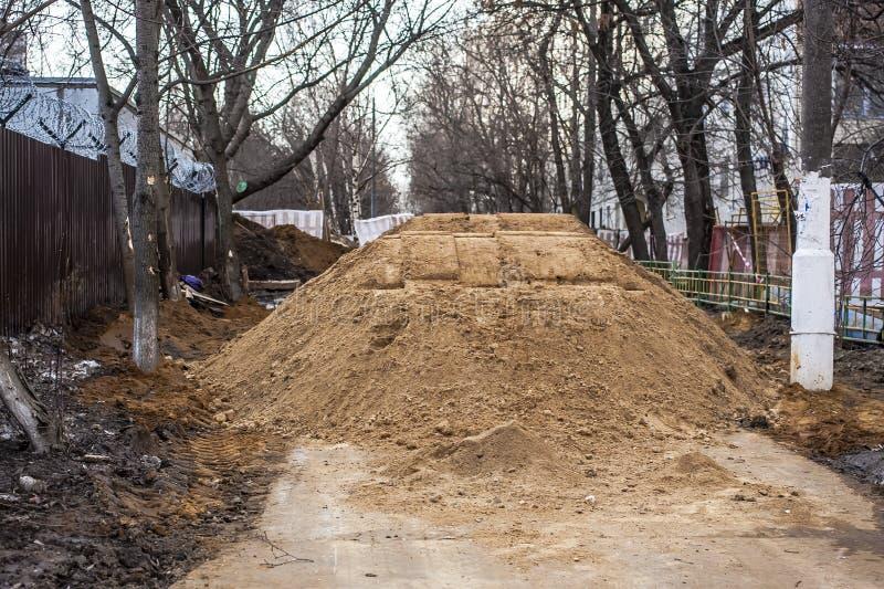 Grande mucchio della sabbia su un sentiero per pedoni I lavoratori hanno sommerso il passaggio I problemi non sono le riparazioni immagine stock libera da diritti