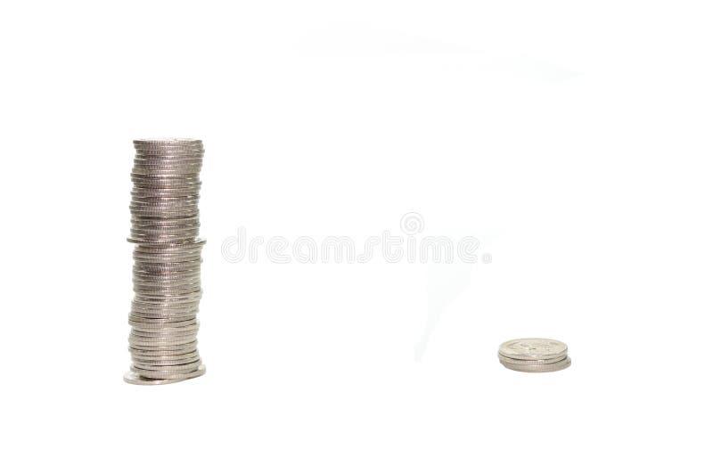 Grande mucchio delle monete contro il piccolo mucchio delle monete fotografie stock libere da diritti