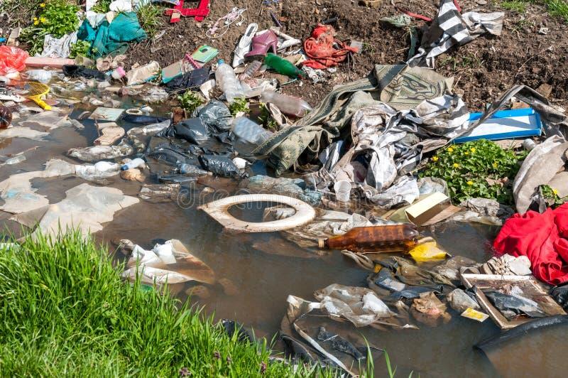 Grande mucchio di immondizia e di ciarpame nell'acqua di fiume che inquina la natura con la lettiera fotografia stock
