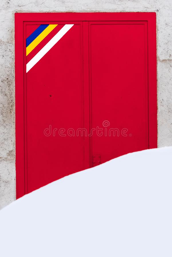 Grande mucchio di neve che riguarda l'entrata di una porta rossa del grande metallo fotografie stock