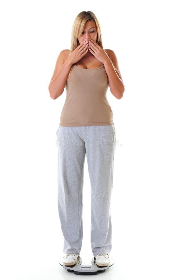 A grande mulher na escala preocupou-se com seu peso foto de stock