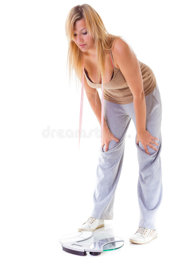 A grande mulher na escala preocupou-se com seu peso isolado fotos de stock