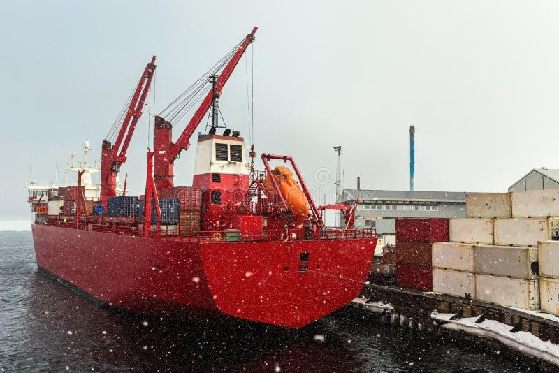 Grande nave da carico rossa nell'ambito delle precipitazioni nevose pesanti nel porto di Aasiaat, Groenlandia fotografie stock